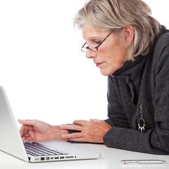 seniorin schaut auf laptop