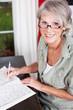 seniorin mit brille löst ein kreuzworträtsel