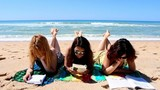 Pretty girls reading books on the beach