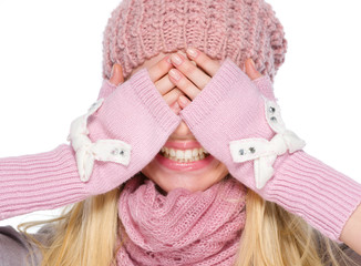 Portrait of girl in winter clothes covering eyes with hands