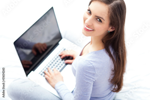 Woman sitting on bed with laptop