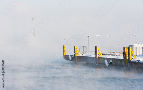 Misty sea and shipping docks in port