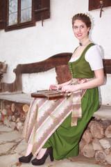 Bayerisches Mädchen beim Zither spielen auf einer Hausbank