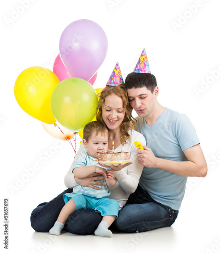 kid boy with parents looking at festive cake with candles