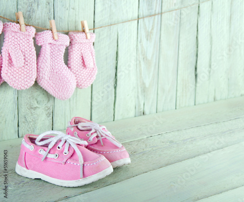 Toddler shoes on wooden vintage background