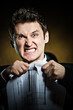 Angry businessman tearing document