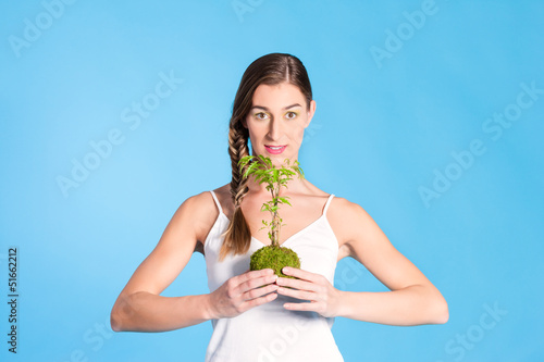 Young Woman holding a small tree
