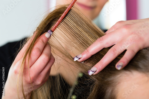 Woman receiving haircut in hairdressers shop