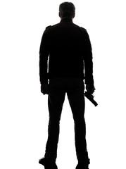 rear view man killer policeman holding gun silhouette