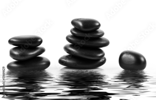 Black massage stones stacked, isolated.