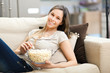 Beautiful young woman eating popcorn on the sofa