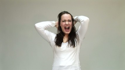 Screaming angry young woman holding her head between hands.