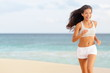 Woman runner running happy on beach