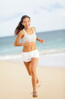 Runner woman running on beach smiling happy