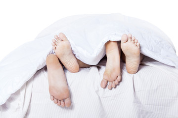 Close-up of the feet couple on bed