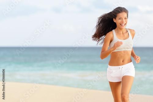 Woman runner running happy on beach