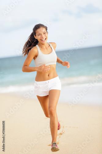 Runner woman running on beach smiling happy