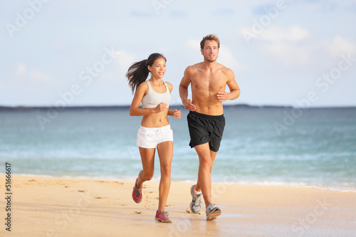 People running - young couple jogging on beach