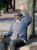 Poor elderly Homeless man waving
