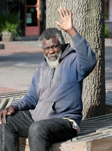 Poor elderly Homeless man waving