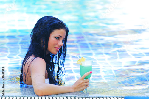Woman in swimming pool with cocktail