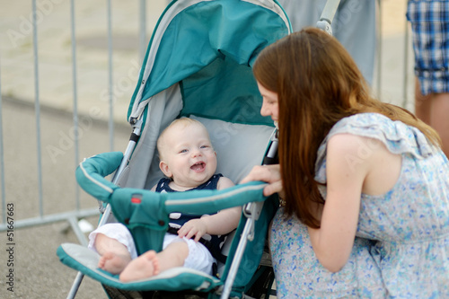 Young mother talking to her baby in a stroller