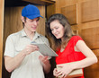 Young courier deliver package to pretty woman