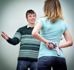 Woman hiding gun underhand talking to man