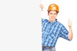 A male worker with helmet posing behind a panel and giving thumb