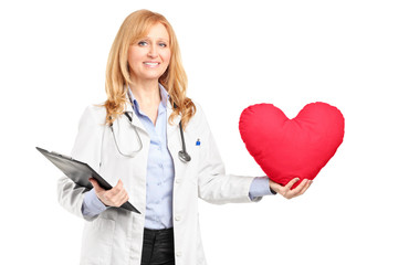 A female doctor holding a red heart