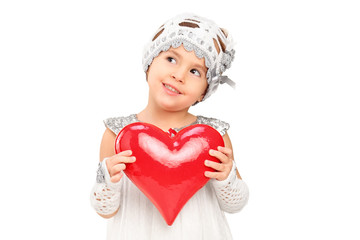 A girl in dress holding a red heart and thinking