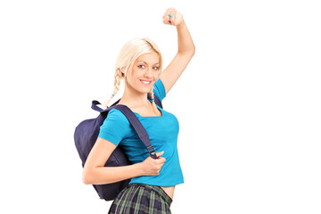 An excited young female student with raised hands