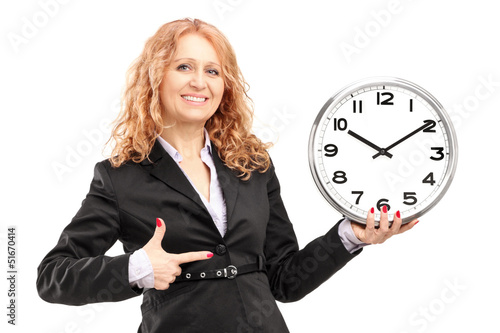 A blond mature woman standing and pointing on a wall clock