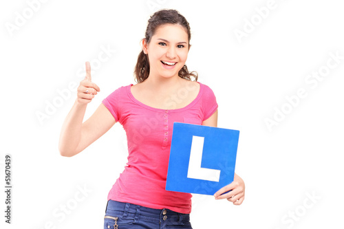 A happy teenager holding L plate and giving a thumb up
