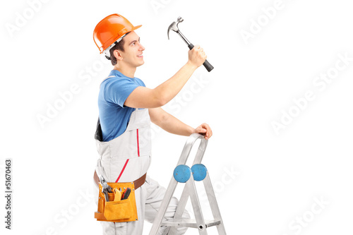A repairman on a ladder working with a hammer