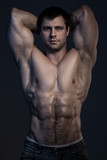 Closeup portrait of muscular guy in dark