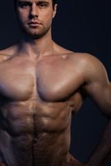 Closeup portrait of muscular guy in dark