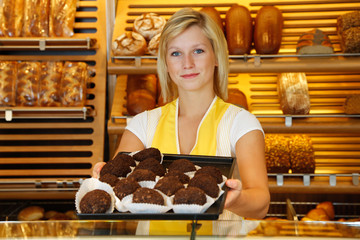 Shopkeeper in bakery presents tablet of rum balls