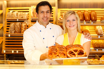 Shopkeeper and baker in Bakery or baker's shop present pretzels