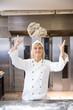 Baker throwing bread dough in bakery or bakehouse