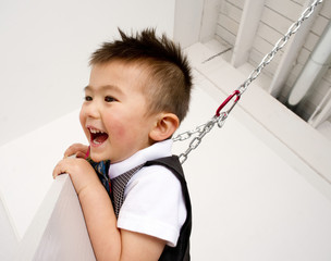 Horizontal Composition Happy Young Boy Playing on Chain Swing Se
