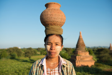 Portrait of Asian traditional farmer carrying pot on head