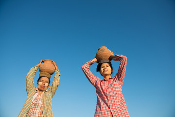 Asian traditional farmers carrying pot on head