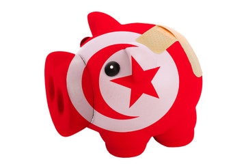 closed piggy rich bank with bandage in colors national flag of t