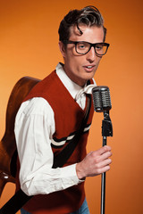 Retro fifties style rock and roll singer with vintage microphone