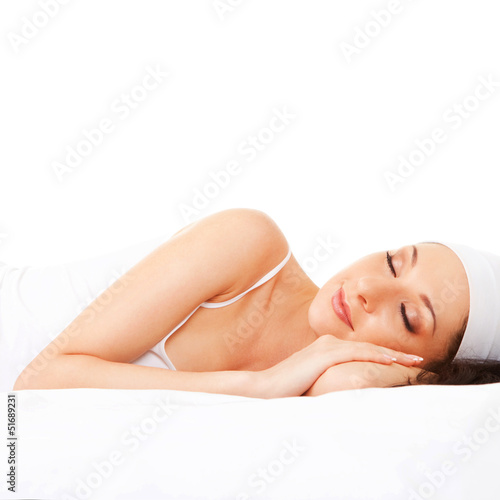 Cute woman sleeps on the white bed