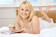 Junge Frau lernt im Bett