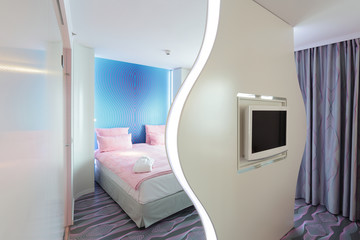 Hotelzimmer mit Bett, Fernseher und Trennwand