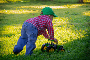 Young Boy Pushing Toy Tractor in Grass