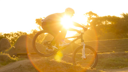 Ciclista en bump a contraluz, atardecer, deporte, bicicleta.